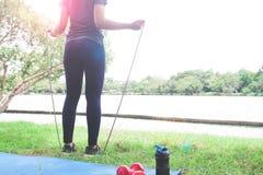 拿着跳绳,健康生活方式的体育衣物的妇女 库存图片