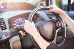 拿着轮子和驾驶在好时光的妇女一辆汽车,有选择性 免版税库存照片
