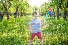 拿着轮转焰火的一个愉快的逗人喜爱的小男孩的画象在公园 库存照片