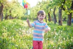 拿着轮转焰火的一个愉快的逗人喜爱的小男孩的画象在公园 图库摄影