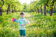 拿着轮转焰火的一个愉快的逗人喜爱的小男孩的画象在公园 免版税图库摄影