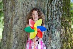 拿着轮转焰火的十几岁的女孩,当倾斜在树干时 免版税库存图片