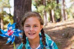 拿着轮转焰火的微笑的女孩在森林里 免版税库存图片