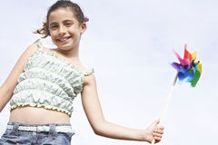 拿着轮转焰火的愉快的女孩反对清楚的天空 免版税库存照片