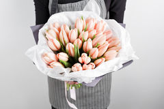 拿着软的桃红色郁金香的妇女手在白色背景开花 用牛皮纸装饰的花束 库存照片