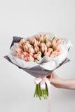 拿着软的桃红色郁金香的妇女手在白色背景开花 用牛皮纸装饰的花束 免版税库存图片