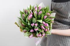 拿着软的淡紫色郁金香的妇女手在白色背景开花 用牛皮纸装饰的花束 免版税图库摄影