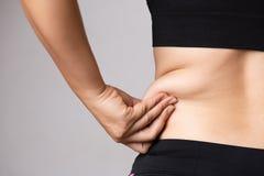 拿着过份腹部油脂的肥胖妇女手 医疗保健和妇女饮食减少腹部和塑造健康的生活方式概念 免版税库存图片