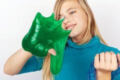 拿着透明蓝色闪烁和绿色软泥在她的手上的女孩 免版税图库摄影