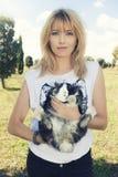 拿着逗人喜爱的宠物兔宝宝的美丽的金发妇女 免版税图库摄影