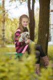 拿着逗人喜爱的小狗的美丽的小女孩 免版税图库摄影