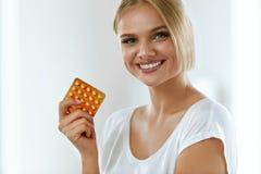 拿着避孕药,口服避孕药的美丽的妇女 免版税图库摄影