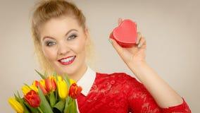 拿着郁金香和礼物的妇女 免版税库存照片