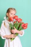 拿着郁金香的微笑的小女孩 免版税库存照片