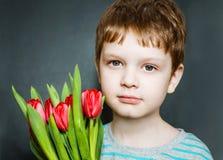 拿着郁金香的花束严肃的男孩。 免版税库存照片