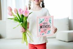 拿着郁金香花束和明信片的微笑的女孩母亲` s天假日 免版税库存图片