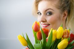 拿着郁金香花的花束妇女 图库摄影