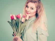 拿着郁金香花的花束妇女 免版税库存照片