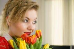 拿着郁金香花的花束妇女 免版税库存图片