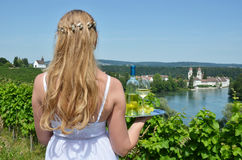 拿着酒和葡萄的女孩反对莱茵河 库存图片