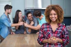 拿着酒的微笑的妇女,当朋友在背景中时 免版税库存图片