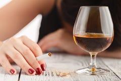 拿着酒精饮料和睡觉与她的在于饮料集中的桌上的头的醉酒的妇女,她的面孔是在焦点外面 免版税库存图片