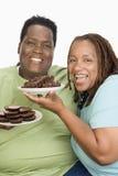 拿着酥皮点心的板材一对肥胖夫妇 免版税库存图片