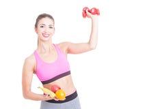 拿着重量和果子在两只手中的女孩 图库摄影