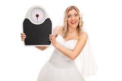 拿着重量标度的快乐的新娘 免版税库存图片