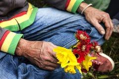 拿着野花的坐的人 库存照片