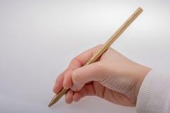 拿着金子颜色铅笔的手手中 免版税库存图片