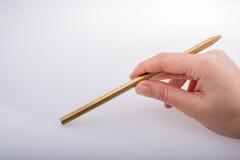 拿着金子颜色铅笔的手手中 图库摄影