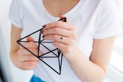 拿着金属几何装饰的美丽的少妇 免版税库存图片