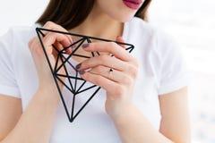 拿着金属几何装饰的美丽的少妇 库存照片