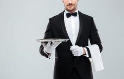 拿着金属空的盘子和餐巾的无尾礼服的侍者 库存照片