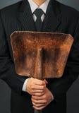 拿着金属铁锹的无法认出的商人 免版税库存照片