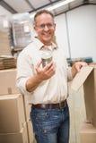 拿着金属锡罐的微笑的仓库工作者 库存照片