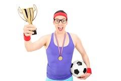 拿着金杯子的讨厌的足球运动员 库存照片