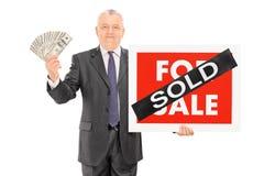 拿着金钱和一个被卖的标志的成熟商人 免版税库存图片