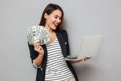 拿着金钱和便携式计算机的愉快的亚裔女商人 免版税库存图片