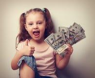 拿着金钱和显示赞许标志的愉快的享用的孩子女孩 库存照片