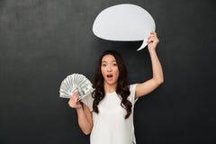 拿着金钱和空白的讲话泡影的T恤杉的震惊妇女 免版税图库摄影
