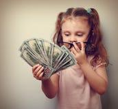 拿着金钱和计数收支的逗人喜爱的企业孩子女孩 免版税图库摄影