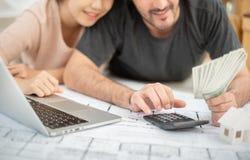 拿着金钱和计算他们的预算的愉快的夫妇 图库摄影