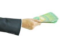 拿着金钱澳大利亚元的手 库存图片