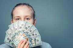 拿着金钱现金在蓝色背景的富有的女孩美元 免版税库存图片