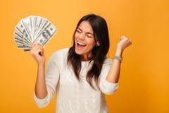 拿着金钱的一个快乐的少妇的画象 图库摄影