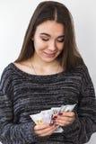 拿着金钱的一名年轻滑稽的妇女的图象 免版税库存照片