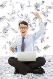 拿着金钱的商人和做一个胜利姿势 免版税库存照片