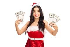 拿着金钱的圣诞老人服装的妇女 库存照片